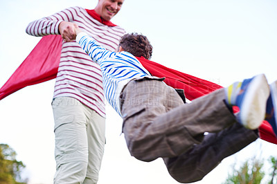 Buy stock photo Shot of a father and his young son pretending to be superheroes while playing outdoors