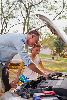 Buy stock photo Shot of a father showing his young son the engine of a car