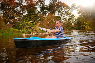 Buy stock photo Shot of a mature man rowing a boat on a lake