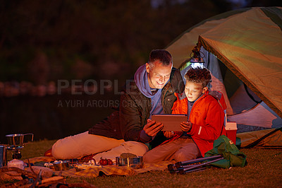 Buy stock photo Shot of a father and son watching a movie on a digital tablet while camping