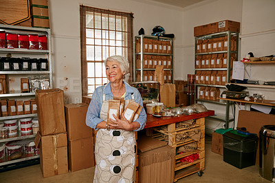 Buy stock photo Cropped shot of a senior woman holding bags of coffee beans while standing in a roastery