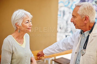 Buy stock photo Shot of a senior woman visiting her doctor