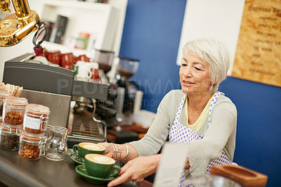 Buy stock photo Shot of a senior woman serving coffee in a cafe