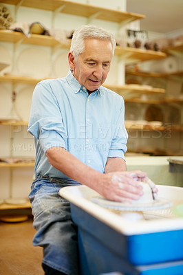 Buy stock photo Shot of a senior man making a ceramic pot in a workshop