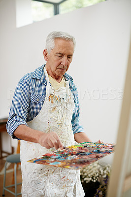 Buy stock photo Shot of a senior man working on a painting at home