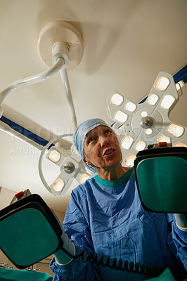 Buy stock photo Shot of a surgeon using a defibrillator during surgery