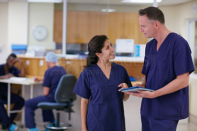 Buy stock photo Shot of two medical practitioners having a conversation in a hospital