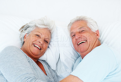 Buy stock photo Closeup portrait of happy senior couple relaxing together in bed and smiling