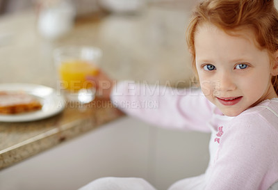Buy stock photo Portrait of a happy little girl smiling at you while holding a glass of juice, having breakfast at home - copyspace