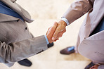 Two businessman shaking hands over a deal
