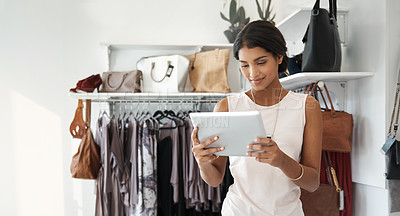 Buy stock photo Shot of a woman using a digital tablet in a clothing store