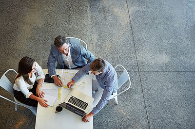 Buy stock photo High angle shot of three businesspeople working in the office