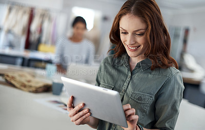 Buy stock photo Shot of a successful young fashion designer using her tablet in her workspace