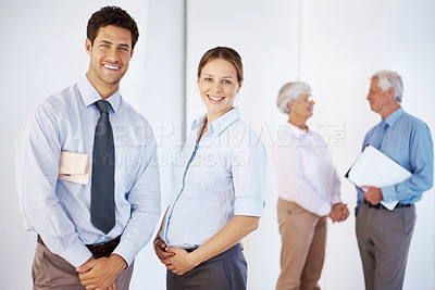 Buy stock photo Successful young business executives with their colleagues talking in the background