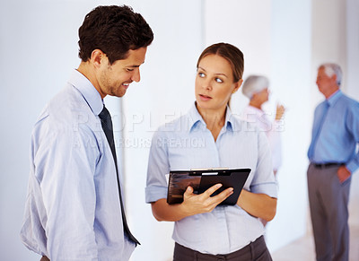 Buy stock photo Two business executives discussing reports with people standing in background