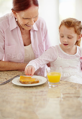 Buy stock photo Portrait of a sweet little girl with her grandmother while having her breakfast