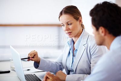 Buy stock photo Smart young businesswoman showing something to her colleague on laptop computer
