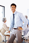 Relaxed businessman standing in front of his team