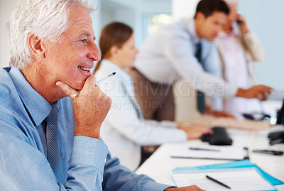 Buy stock photo Portrait of a happy old businessman working in office with colleagues in background
