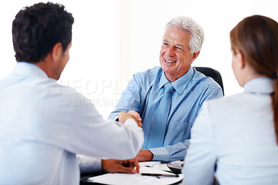 Buy stock photo Senior financial advisor shaking hands with a young couple