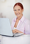 Smiling mature woman working on a laptop