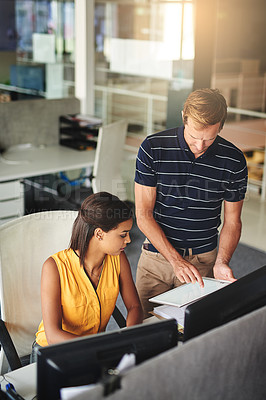 Buy stock photo Shot of two colleagues working together in an office