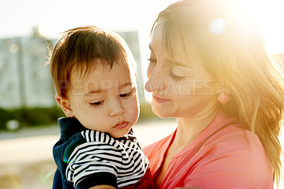 Buy stock photo Shot of a mother and her baby boy spending the day at the beach