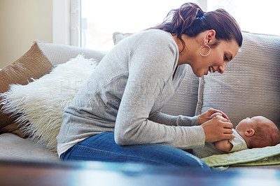 Buy stock photo Shot of a mother sitting with her newborn baby on a couch