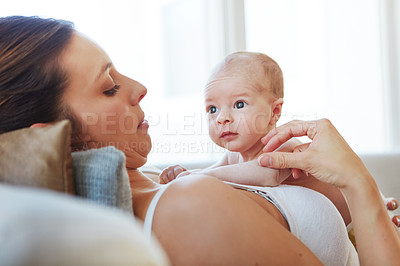Buy stock photo Shot of a mother lying down with her newborn baby on top of her