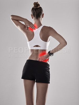Buy stock photo Shot of a young woman holding her injured back and shoulder that's highlighted in red