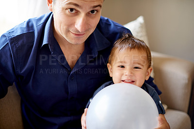 Buy stock photo Portrait of a father and his little son playing with a balloon at home