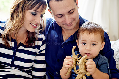 Buy stock photo Portrait of an adorable little boy playing with a toy dinosuar on the couch with his parents at home
