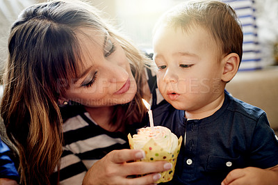 Buy stock photo Shot of an adorable little boy having a cupcake on his first birthday with his mother at home