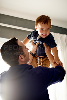 Buy stock photo Shot of a happy father and his adorable son bonding at home