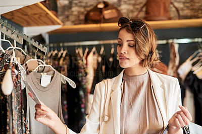 Buy stock photo Shot of a young woman looking at a few items in a boutique
