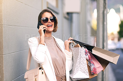 Buy stock photo Shot of a young woman using her cellphone while standing in front of a building with a bunch of shopping bags