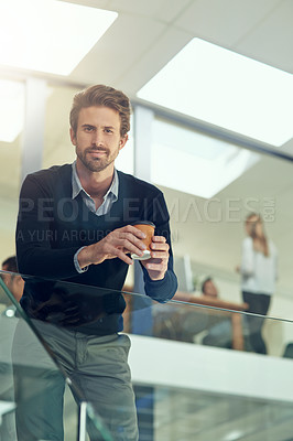 Buy stock photo Portrait of a young businessman drinking a coffee while leaning on a railing in an office
