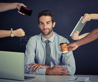 Buy stock photo Portrait of a young corporate businessman sitting at a desk surrounded by hands reaching in with office items