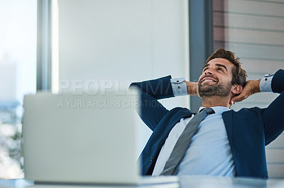 Buy stock photo Shot of a young corporate businessman taking a break at an office desk