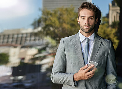 Buy stock photo Portrait of a handsome young businessman leaning against a glass wall using a cellphone