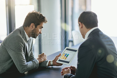 Buy stock photo Shot of two colleagues looking at a graph on a digital tablet together in an office