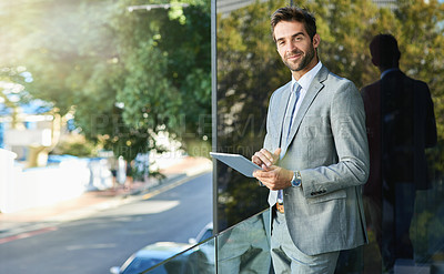 Buy stock photo Portrait of a handsome young businessman using a digital tablet outside