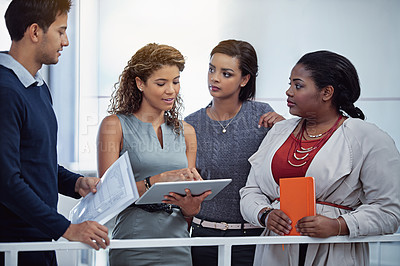 Buy stock photo Shot of a group of colleagues working together on a digital tablet in an office