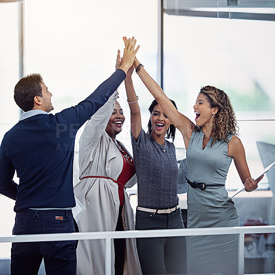 Buy stock photo Shot of a group of colleagues high fiving together in an office