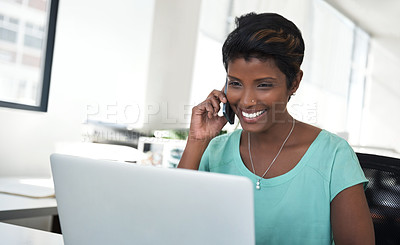Buy stock photo Shot of an ambitious woman using a phone and laptop at her desk in a modern office