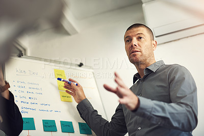 Buy stock photo Shot of a man giving a presentation to colleagues in an office