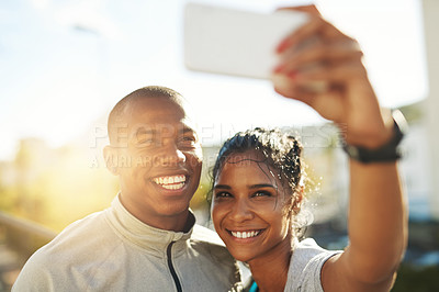 Buy stock photo Shot of a young sporty couple taking a photo together with a cellphone