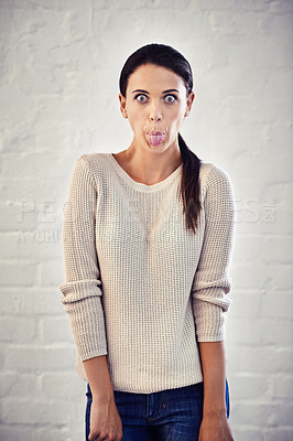 Buy stock photo Portrait of a young woman sticking out her tongue