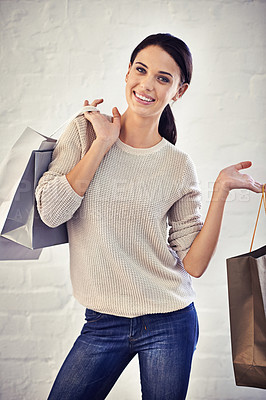 Buy stock photo Shot of a casually dressed young woman holding shopping bags standing against a brick wall