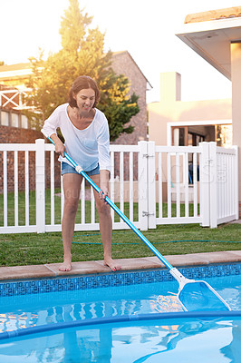 Buy stock photo Shot of a young woman cleaning a pool